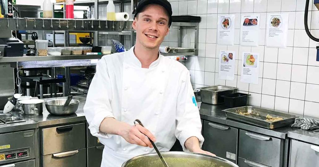 Ravintola-alaa opiskeleva kokki keittokattilan ääressä