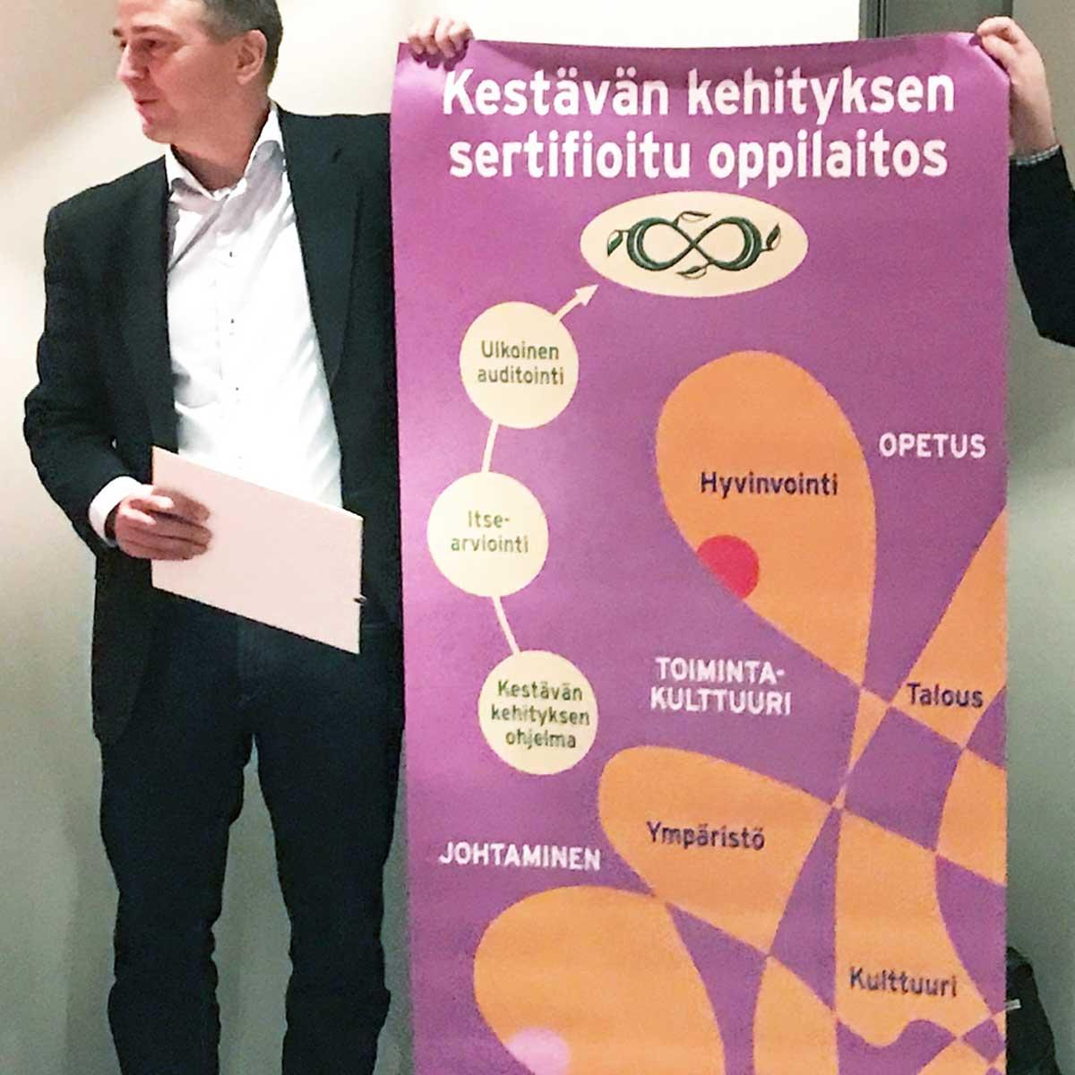 Rehtori Juha Ojajärvi pitelee OKKA-säätiön luovuttamaa Kestävän kehityksen sertifioitu oppilaitos -julistetta