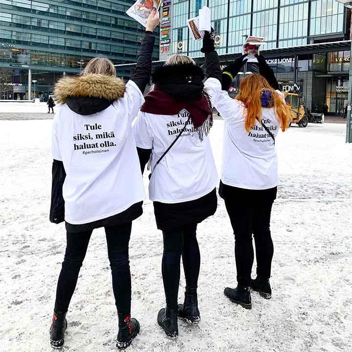 Kolme opiskelijaa Kampin aukiolla jakamassa Ravintola Perhon mainoslehtisiä