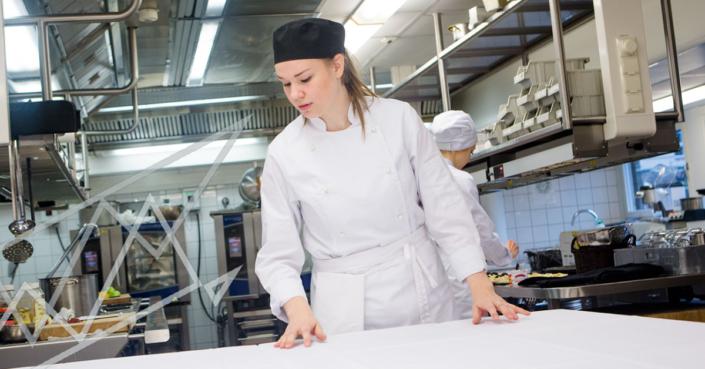 Kokkiopiskelija liinoittaa ruokapöytää Perho Liiketalousopistossa. Kokin opintoihin lukiopohjalta.